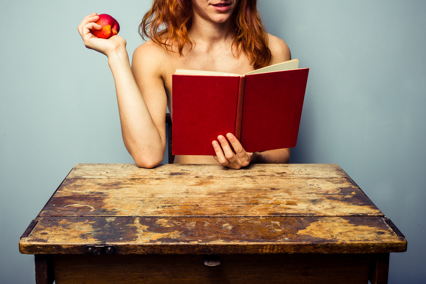 Naked woman reading and eating a peach